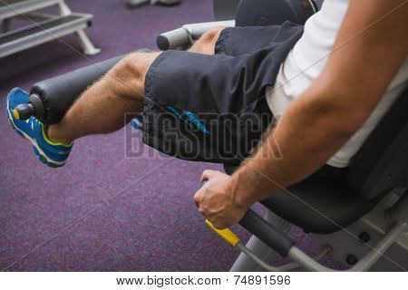 Side view low section of a man doing leg workout at the gym