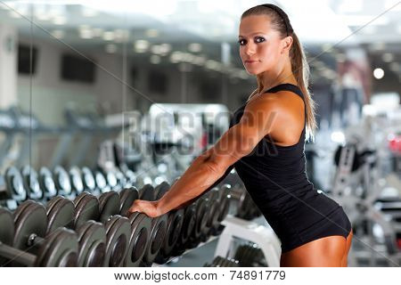 Young woman bodybuilder with dumbbell.