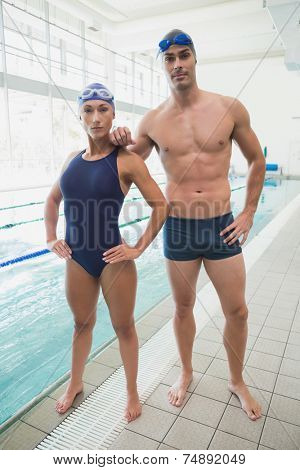 Portrait of a fit male and female swimmers by the pool at leisure center