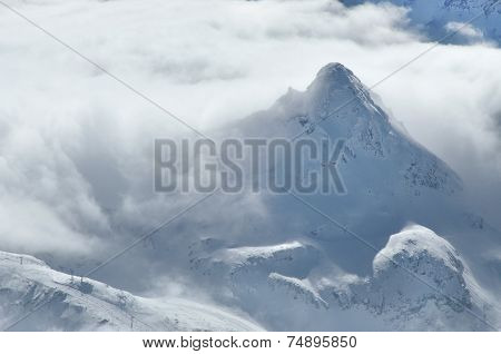 Winter In The Alps With Clouds Above The Mountains