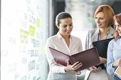 pic of file folders  - Businesswomen with file folders discussing in office corridor - JPG