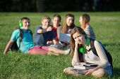 picture of depressed teen  - Pouting teen girl near group on grass outdoors - JPG