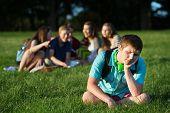 picture of peer-pressure  - Group of teen bullying sad student sitting outdoors - JPG