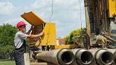 picture of rig  - Oil and gas well drilling worker operates drilling rig machinery - JPG