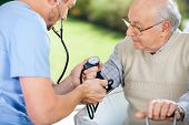 foto of nurse  - Male nurse checking blood pressure of senior man at nursing home - JPG