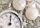 stock photo of pendulum clock  - clock striking midnight in silver holiday decor - JPG