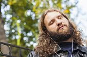 foto of long beard  - Blond long hair and beard young adult hipster man listening music. Outdoor, urban scene. ** Note: Shallow depth of field - JPG