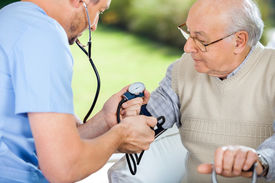 image of nursing  - Male nurse checking blood pressure of senior man at nursing home - JPG