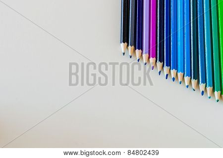 Blue Spectrum Pencil Crayons Lined Up Diagonally Top Right Corner On White Background