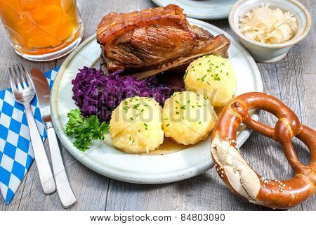 Appetizing Bavarian roast pork dish with dumplings and pretzel