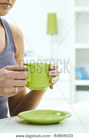 Close up of woman having a cup of tea at home. Holding mug in hand, ring on finger, high key, copyspace. Pastel colors.