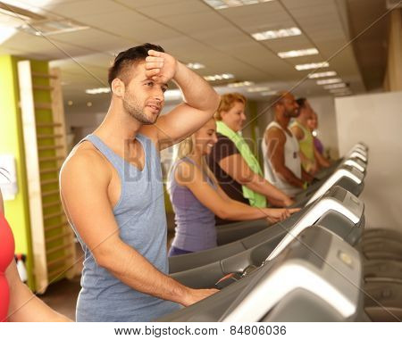 Young people training in running machine in gym.