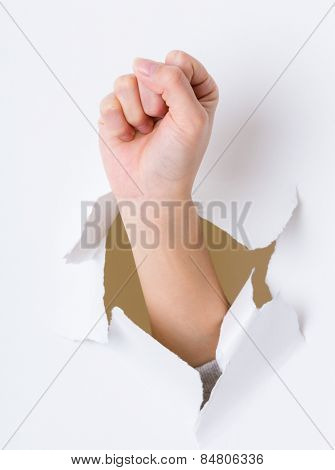 Arm fist breaking through the paper wall