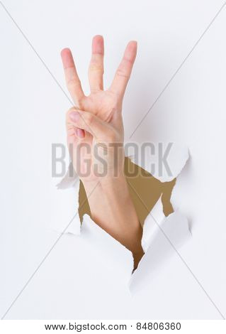 Three finger breaking through paper wall