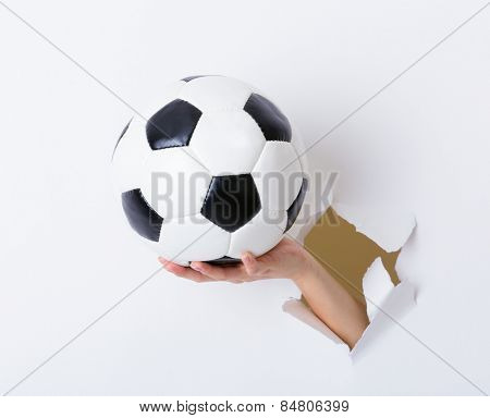 Soccer ball hold with woman hand break through the paper wall
