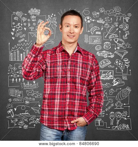 Asian man smiling and showing OK, choosing between family, relations, hobbies, work and sport, on sketch background