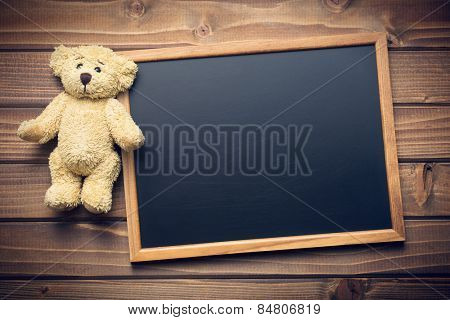 blank chalkboard and teddy bear on wooden table