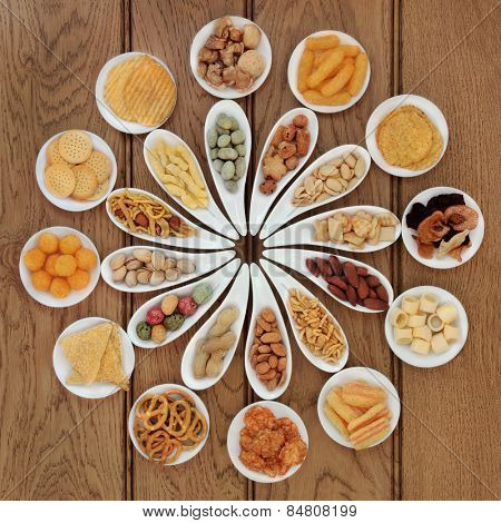 Savoury snack food selection in porcelain dishes over oak background.