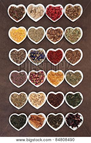 Large herb tea selection in heart shaped porcelain bowls over lokta paper background.