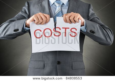 Businessman Tearing The Word Costs On Paper