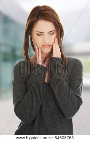 Woman pressing her cheek because of toothache