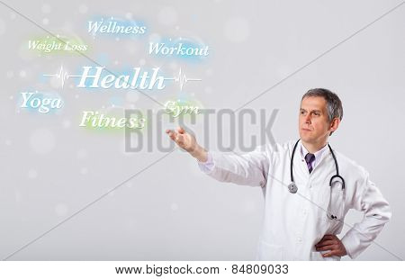 Elderly clinical doctor pointing to health and fitness collection of words