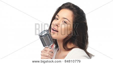 Preety woman with long brown hair standing singing into a microphone and looking seductively at the camera, over white