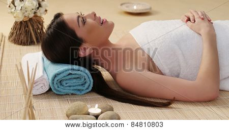 Close up Long Hair Young Woman Lying Down in a Spa with White Towel Cover on her Body.