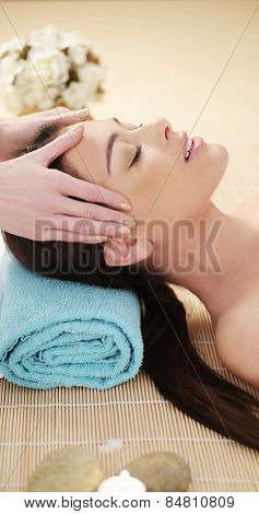 Attractive young woman having a head massage in a spa smiling with enjoyment as the masseuse massages her temples with her fingertips