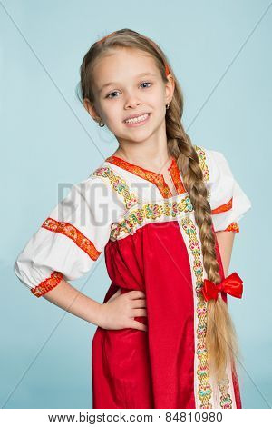 Blond girl with a scythe in the traditional Russian folk costume. Girl seven years.