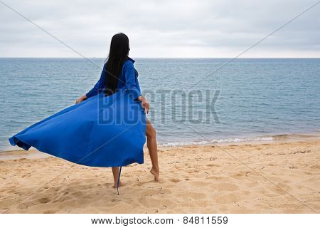Beautiful young woman in a dress and a swimsuit on the beach