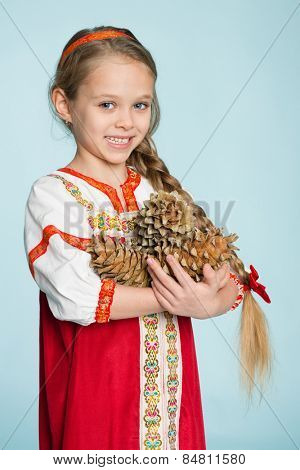 Beautiful girl in a traditional Russian folk costume with pine cones in his hands. Girl seven years.