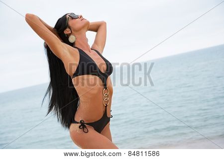 Beautiful young woman in a black bathing suit on a background of the sky near the sea