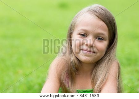Portrait of a wonderful little girl on a green background. Girl seven years.