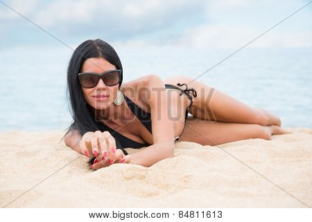 Tanned young girl in a black bathing suit lying on the sand