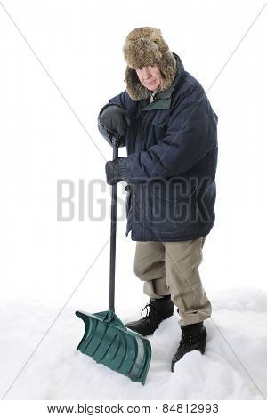 A bundled, senior adult man looking at the viewer as he stands with his shovel in the snow.  On a white background.