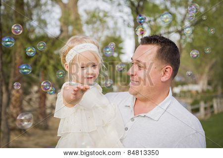 Affectionate Father Holding Cute Baby Girl Enjoying Bubbles Outside at the Park.