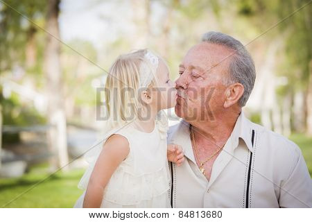 Loving Grandfather and Granddaughter Kissing Outside At The Park.