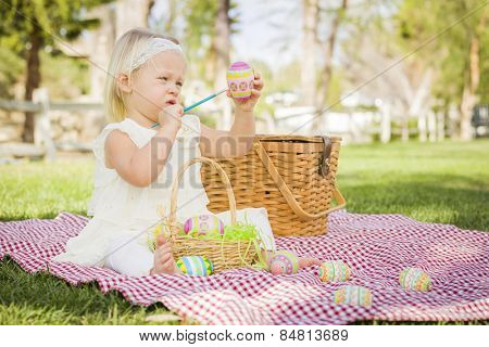 Cute Baby Girl Enjoys Coloring Her Easter Eggs on Picnic Blanket in the Grass.
