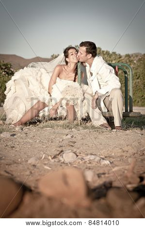 happy newly wed couple outdoors on playground having fun