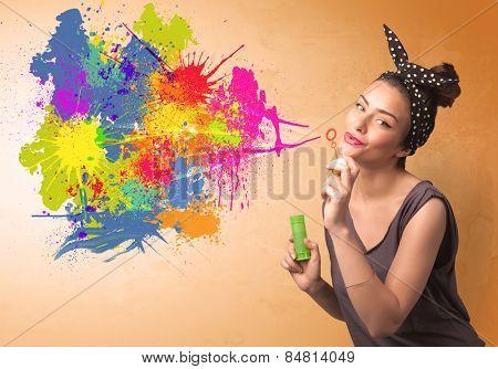 Cute girl blowing bubble spalsh graffiti into wall