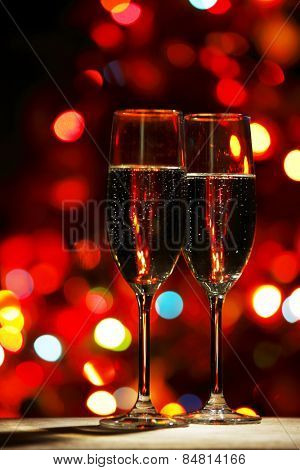 Two champagne glasses on color bokeh background