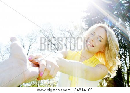 Happy woman holding by hands and whirling in park