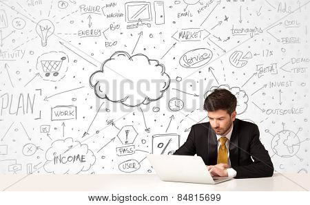 Businessman sitting at white table with hand drawn business concept background