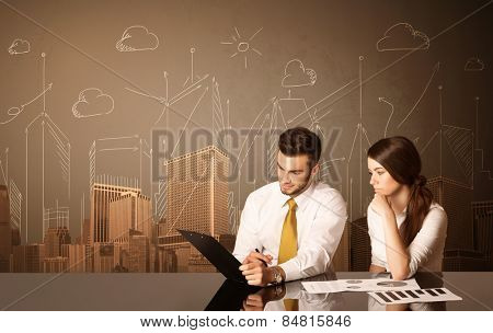 Business couple sitting at the black table with buildings and measurements on the background