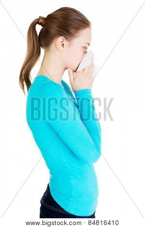 Young beautiful blonde woman sneezing