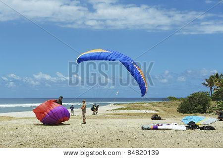 Paragliders land at the Indian ocean shore, Reunion.