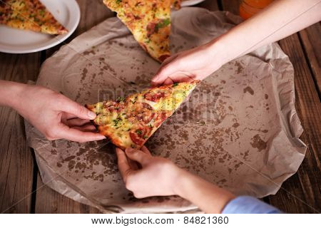 Friends hands taking slice of pizza
