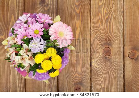 Colorful flowers bouquet on wooden table. Top view with copy space