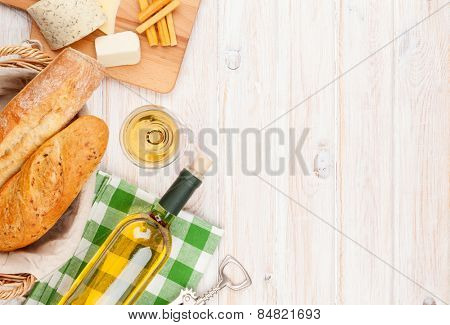 White wine, cheese and bread on white wooden table background. Top view with copy space